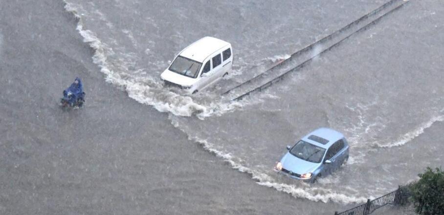 7月20日,车辆在郑州街头涉水前行